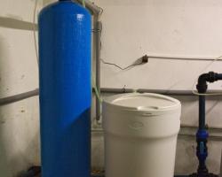 Změkčovač vody AquaSoftener vedle s roztokem solanky
